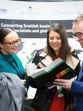 Three delegates browsing through ScotExport 2018 programme