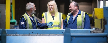 Rosie Hill from Ireland Alloys with Danny McKillop on left and Scott Dobbie on right, all wearing hi-vis vests